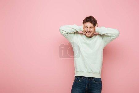 Photo pour Homme choqué couvrant les oreilles avec les mains tout en grimacant avec les yeux fermés sur fond rose - image libre de droit