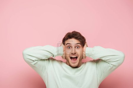 Photo for Scared man screaming while covering ears with hands on pink background - Royalty Free Image