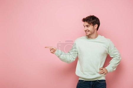Photo pour Joyeux jeune homme regardant loin et pointant du doigt tout en tenant la main sur la hanche sur fond rose - image libre de droit