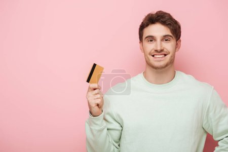Photo for Happy young man holding credit card while smiling at camera on pink background - Royalty Free Image