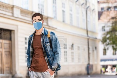 Photo for Handsome man with illustrated face in medical mask and hands in pockets on street - Royalty Free Image