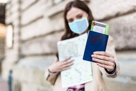 Photo for Selective focus of woman in medical mask holding map and showing passport and air ticket with quarantine illustration - Royalty Free Image