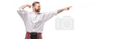 happy Scottish redhead man in red kilt pointing with finger aside isolated on white, panoramic crop