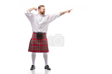 Photo pour Heureux écossais rousse homme en rouge kilt pointant avec le doigt de côté sur fond blanc - image libre de droit
