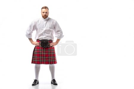 serious Scottish redhead man in red kilt with hands on hips on white background