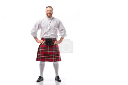 smiling Scottish redhead man in red kilt with hands on hips on white background