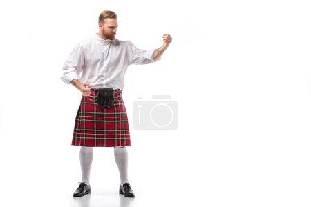 серьезный шотландский рыжий мужчина в красном килте на белом фоне