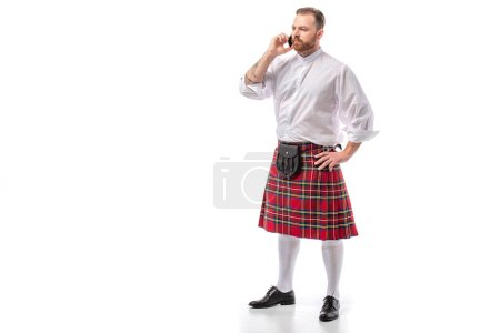 serious Scottish redhead man in red kilt talking on smartphone on white background