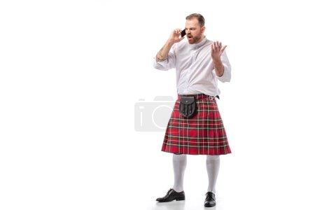 Photo pour Irrité écossais rousse homme en kilt rouge parler sur smartphone sur fond blanc - image libre de droit