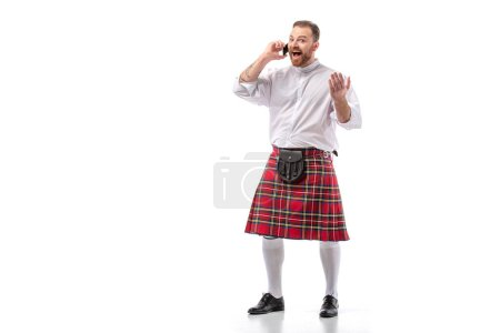 excited Scottish redhead man in red kilt talking on smartphone on white background