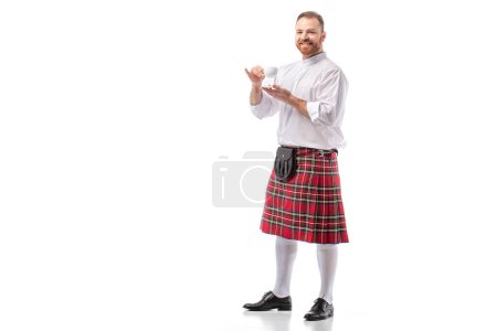 smiling Scottish redhead man in red kilt drinking coffee on white background