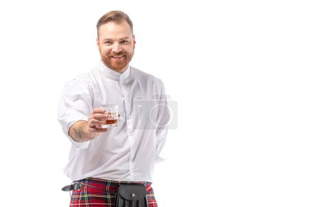 smiling Scottish redhead man in red kilt with whiskey in glass isolated on white
