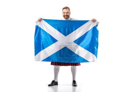 Photo pour Red-head écossais souriant en kilt rouge avec drapeau d'Écosse sur fond blanc - image libre de droit