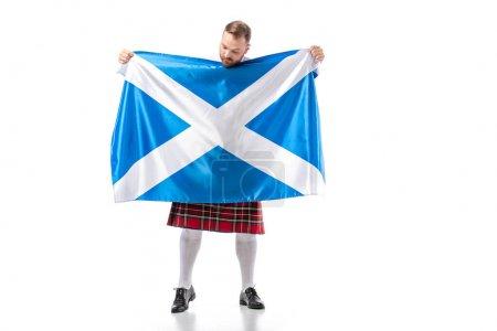 Photo pour Rouge écossais en kilt rouge regardant le drapeau d'Écosse sur fond blanc - image libre de droit