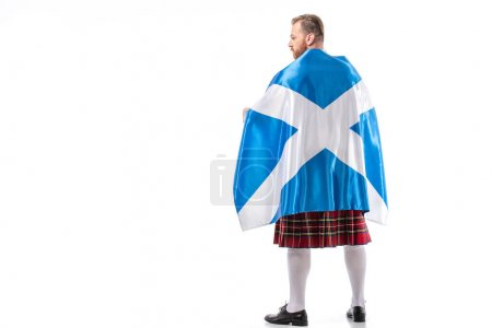 Photo pour Back view of Scottish redhead man in red kilt with flag of Scotland on white background - image libre de droit