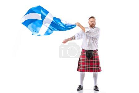 Photo pour Roux écossais en kilt rouge avec drapeau d'Écosse sur fond blanc - image libre de droit