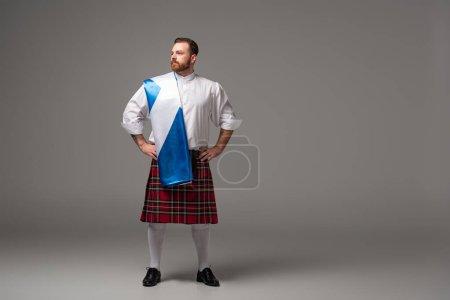Photo pour Homme roux écossais sérieux en kilt rouge avec drapeau d'Écosse et les mains sur les hanches sur fond gris - image libre de droit