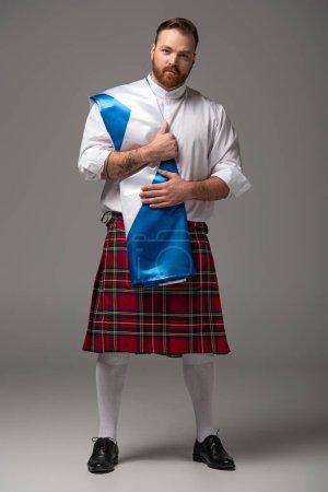 Photo pour Roux écossais en kilt rouge avec drapeau d'Écosse sur fond gris - image libre de droit