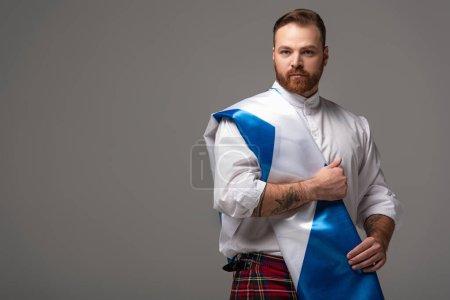 Photo pour Homme roux écossais sérieux en kilt rouge avec drapeau d'Écosse sur fond gris - image libre de droit