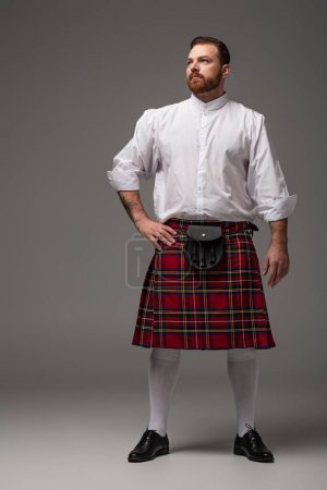 Scottish redhead man in red kilt with hand on hip looking away on grey background