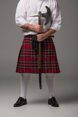 обрезанный вид шотландца в красном килте с боевым топором на сером фоне