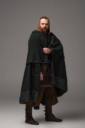 Photo pour Rousse écossaise médiévale homme en manteau sur fond gris - image libre de droit
