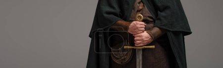 Photo pour Vue recadrée du chevalier écossais médiéval en manteau avec épée dans les mains sur fond gris, prise de vue panoramique - image libre de droit