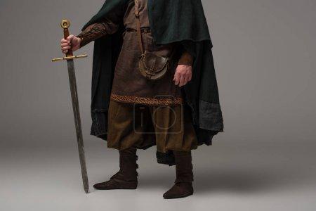 Photo pour Vue recadrée du chevalier écossais médiéval en manteau avec épée sur fond gris - image libre de droit