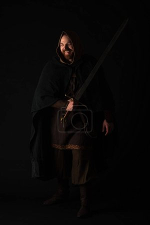 Photo for Happy medieval Scottish redhead man in mantel with sword on dark isolated on black - Royalty Free Image