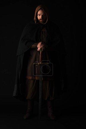 Photo pour Médiéval écossais homme dans mantel avec épée dans sombre isolé sur noir - image libre de droit