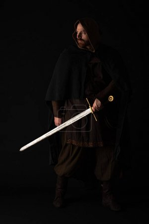 Photo for Medieval Scottish man in mantel with sword in dark isolated on black - Royalty Free Image