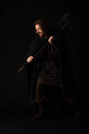 Photo pour Guerrier écossais souriant médiéval avec hache de combat dans manteau isolé sur noir - image libre de droit