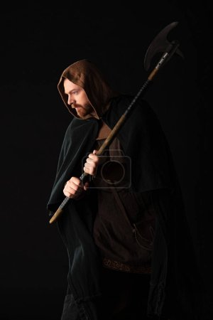 Photo pour Guerrier écossais médiéval avec hache de combat dans manteau isolé sur noir - image libre de droit