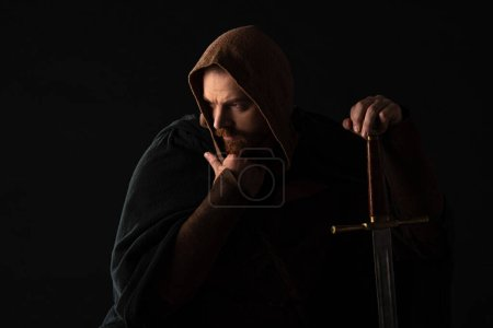 Photo for Frowning medieval Scottish man in mantel with sword  in dark isolated on black - Royalty Free Image