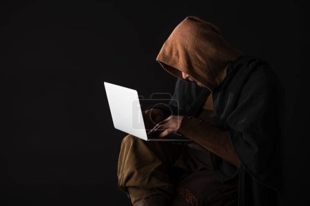 medieval Scottish man in mantel using laptop in dark isolated on black