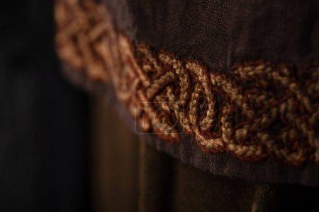 Photo pour Vue rapprochée des vêtements marron écossais médiévaux avec broderie - image libre de droit