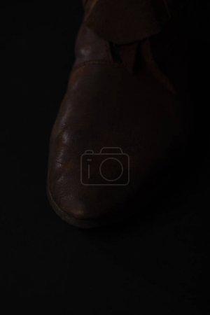Photo pour Vue rapprochée de chaussures en cuir brun écossais médiéval isolé sur noir - image libre de droit
