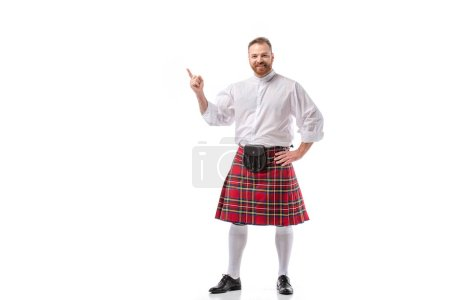 smiling Scottish redhead bearded man in red tartan kilt pointing with finger on white background