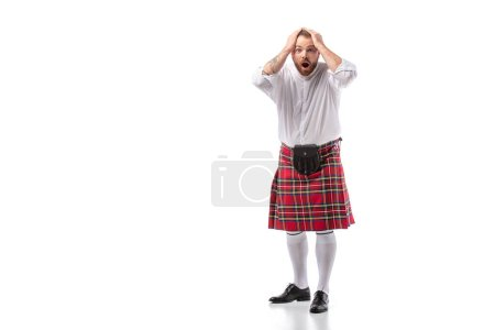 shocked Scottish redhead bearded man in red tartan kilt holding head with open mouth on white background