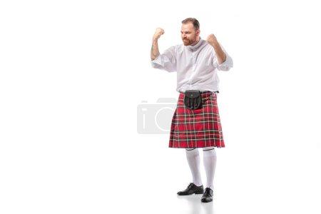 Шотландский рыжеволосый бородатый мужчина в красном тартановом килте показывает да жест на белом фоне