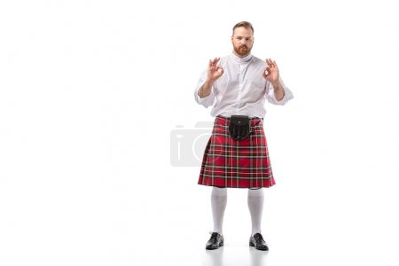 Photo for Scottish redhead bearded man in red tartan kilt showing ok gestures on white background - Royalty Free Image