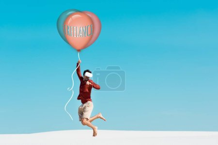 Photo for Man on sandy beach in vr headset flying on balloon with freelance lettering against clear blue sky - Royalty Free Image