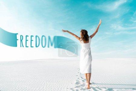 Photo pour Vue arrière de belle fille en robe blanche avec les mains dans l'air sur la plage de sable avec ciel bleu, illustration de la liberté - image libre de droit