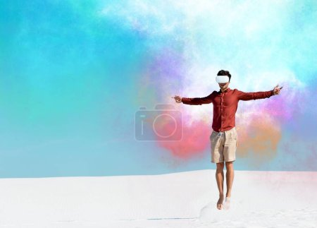Photo for Man on sandy beach in vr headset jumping against clear blue sky, colorful clouds illustration - Royalty Free Image