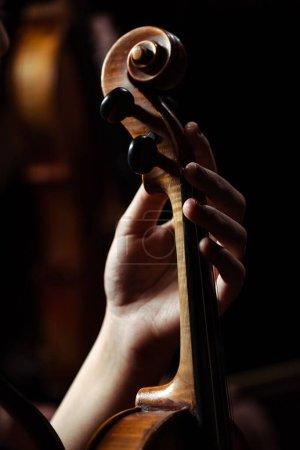 Photo pour Vue recadrée d'une musicienne jouant du violon sur scène sombre - image libre de droit