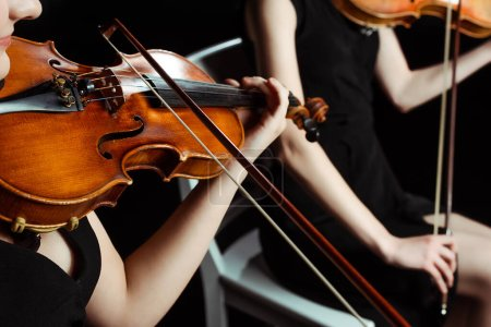 cropped view of two female professional musicians playing on violins on dark stage