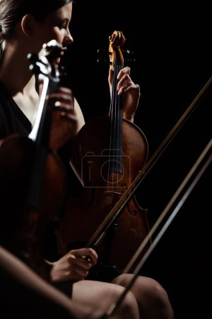 two professional female musicians playing classical music on violins on dark stage