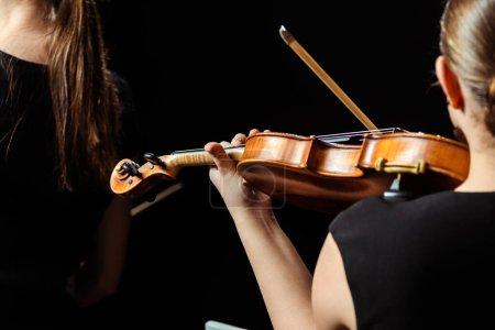 Photo pour Arrière vue recadrée de deux musiciennes professionnelles jouant sur violons sur scène sombre - image libre de droit