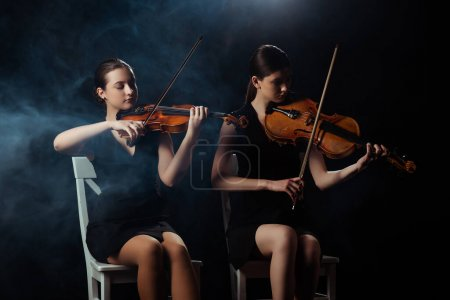 Photo for Attractive musicians playing on violins on dark stage with smoke - Royalty Free Image