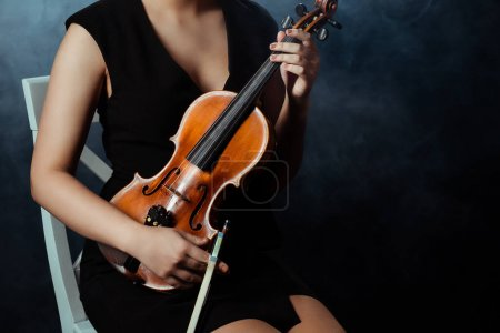 Photo for Cropped view of musician playing on violin on dark stage with smoke - Royalty Free Image